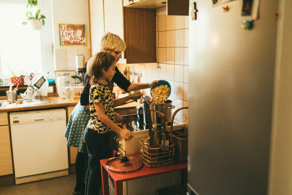 Eine Mütterpflegerin kennt sich mit gesunder Familienernährung aus und bezieht auch Geschwisterkinder spielerisch ins Kochen mit ein.