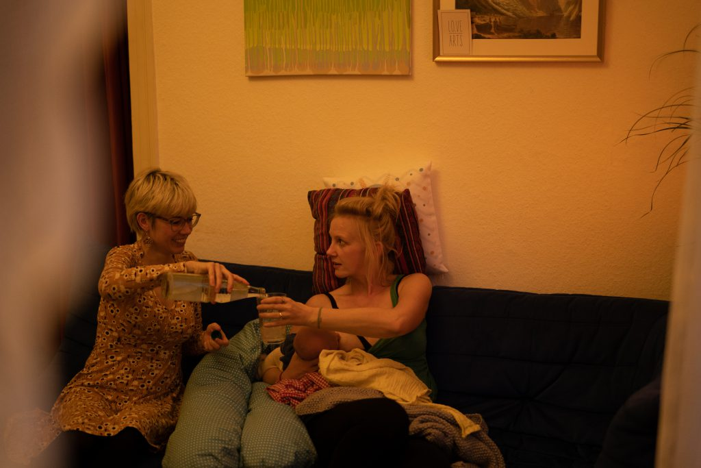 Eine Mütterpflegerin kennt sich mit der geeigneten Ernährung für Stillende aus und achtet darauf, dass die Mutter gut abgestützt sitzt und genug zu trinken hat