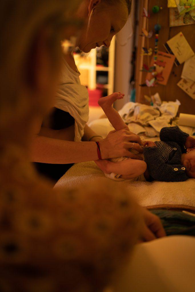 Mutter im Wochenbett - eine Mischung aus Chaos und Glück. Das Shirt ist noch hochgezogen vom Stillen, da wird schon wieder das Baby gewickelt.